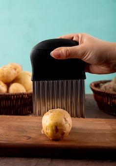 Вид сбоку женщина режет картошку на доске со свеклой в корзине