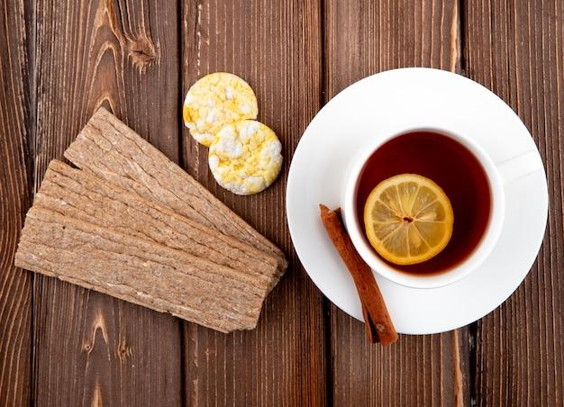 Чашка чая сверху с ломтиком лимона и корицы с печеньем и хрустящим хлебом