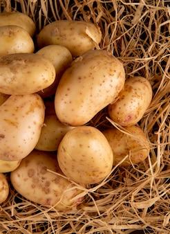 干し草の上面の若いジャガイモ