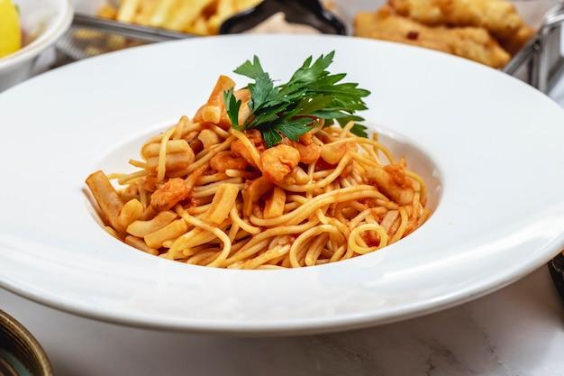 Морепродукты спагетти с кальмарами и креветками в томатном соусе с видом на петрушку