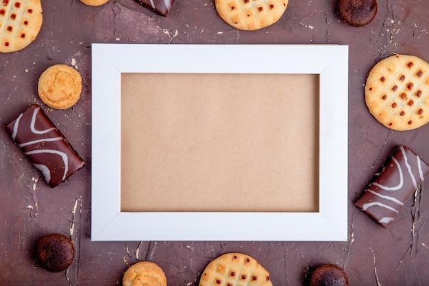 空のフォトフレームと周りのさまざまなクッキーの平面図