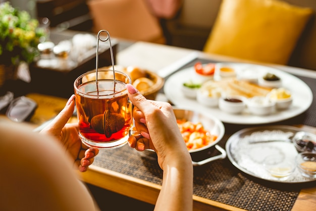 Женщина держит чашку черного чая и завтрак на столе