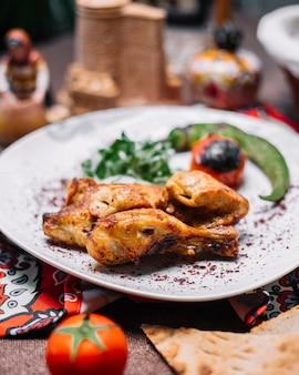 Вид сбоку куриный шашлык с жареным зеленым перцем на гриле томатной зеленью и луком на лаваше