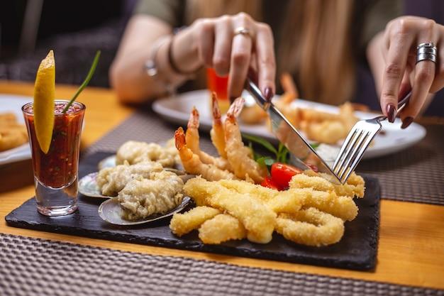 Вид сбоку жареные на гриле морепродукты кальмары кольца мидии креветки соусом и ломтиком лимона