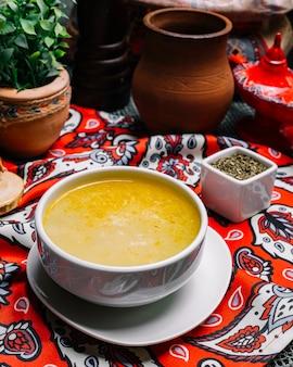 Вид сбоку бульон из баранины с сушеной мятой на столе