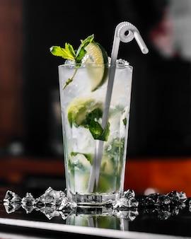 Вид сбоку коктейль ром мохито с мятным лаймом и соломой в бокале