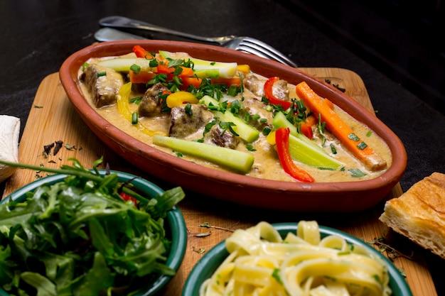 クリーミーなソースにんじんピーマンセロリ野菜側面図を魚します。