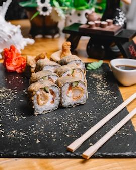 Вид сбоку ролл суши темпура с лососем, огурцом, имбирем, соевым соусом из васаби и семенами кунжута на подносе