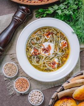 Вид сверху фасолевый суп с жареной луковой лапшой, фасолью, сметаной, черным перцем и зеленью на столе
