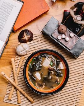 Вид сверху грибной суп из тофу с зеленым луком и хлебными палочками на столе