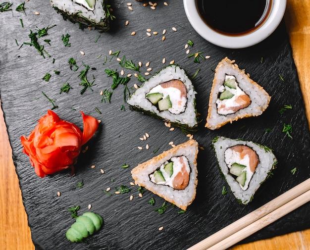 Вид сверху суши ролл с лососем, сливочным сыром, огурцом, имбирем васаби и соевым соусом на доске