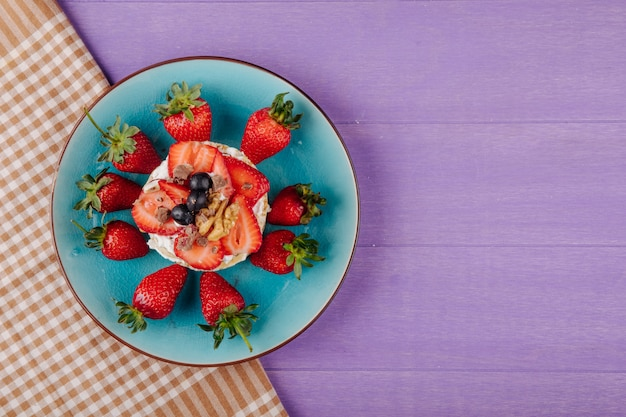 コピースペースを持つ紫色の木製の背景にセラミックプレートに熟したブルーベリーイチゴとサワークリームとナッツのおいしいクリスプブレッドのトップビュー