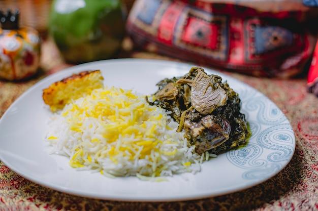 Вид сбоку плов с тушеным мясом и зеленью на белой тарелке