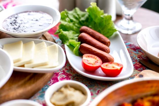 サイドビュー朝食は、トマトとチーズのサラダの葉の上のテーブルフライソーセージを提供しています
