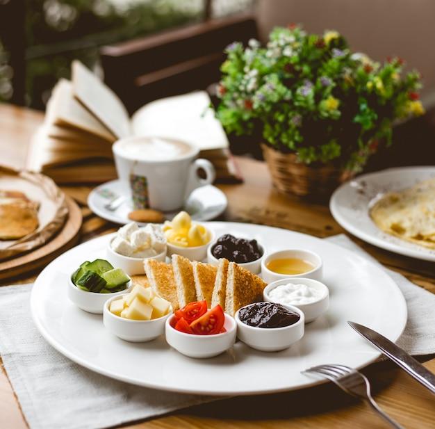 サイドビューの朝食スナック、フライドトースト、トマト、キュウリ、バタージャム、ハニーチーズ