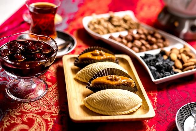 Вид сбоку традиционные азербайджанские сладости пахлава и шекербур с джемом и стаканом чая