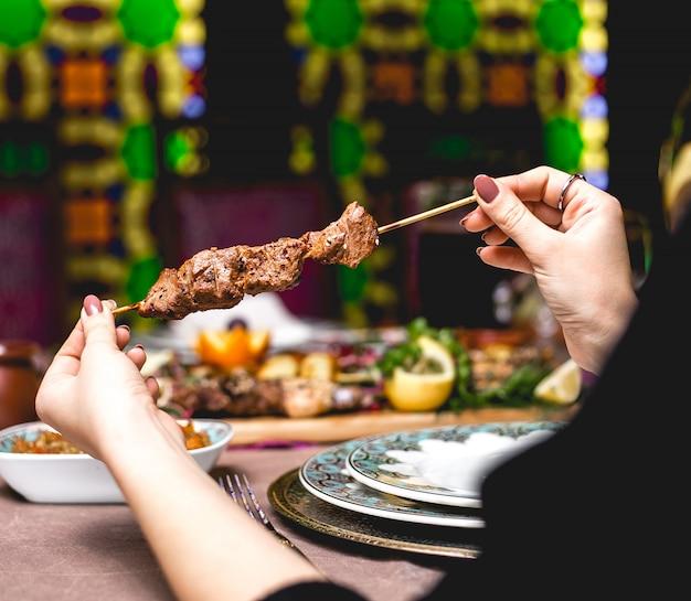 側面図女性が串にケバブ肉を食べる