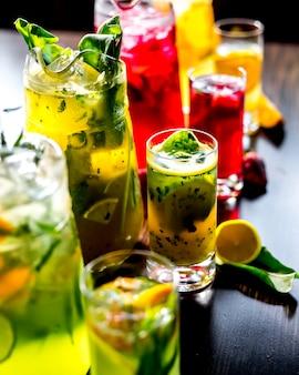 テーブルの上のレモンとイチゴのスライスとさまざまな清涼飲料を活性化する側面図
