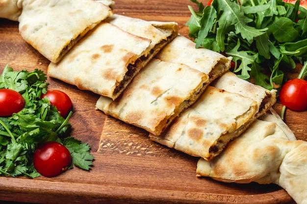 Соде вид сырного пиджа с мясом, луком, помидорами черри и рукколой на подносе