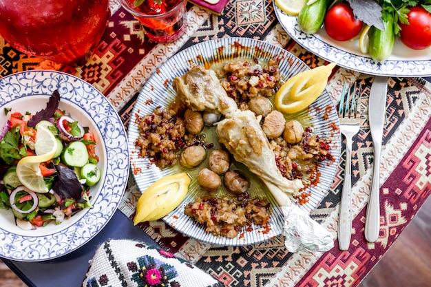 Вид сверху запеченная баранья ножка с каштанами, рубленым мясом, лимоном и овощным салатом