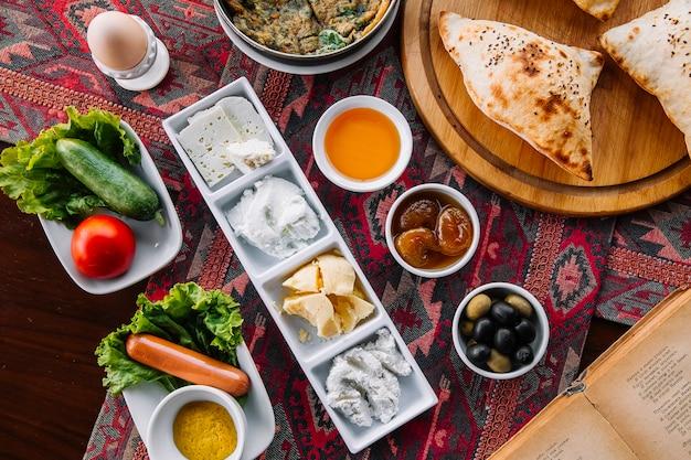 Вид сверху на завтрак варенье из медового масла, сыры, творожные колбаски, яичные овощи и воздушный хлеб