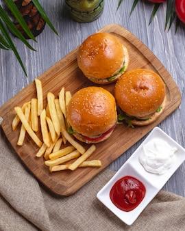 Вид сверху гамбургеры с картофелем фри, кетчупом с майонезом и помидорами