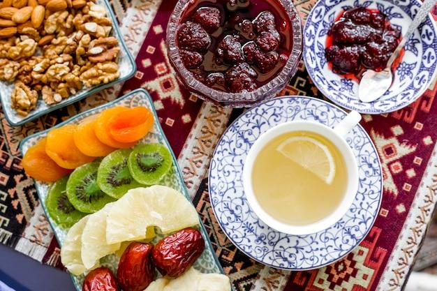 Вид сверху чашка зеленого чая с ломтиком лимона сушеных фруктов и клубничным вареньем