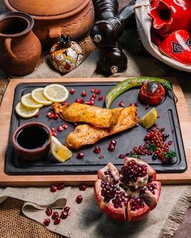 Вид сверху жареная рыба с нарезанным гранатом ‹лимон и овощи гриль с гранатовым соусом