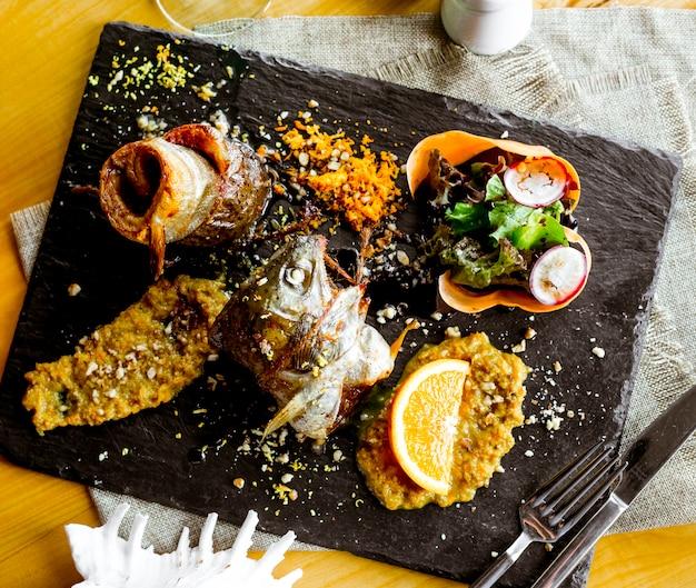 Вид сверху жареная рыба с соусом и ломтиком апельсина с овощами