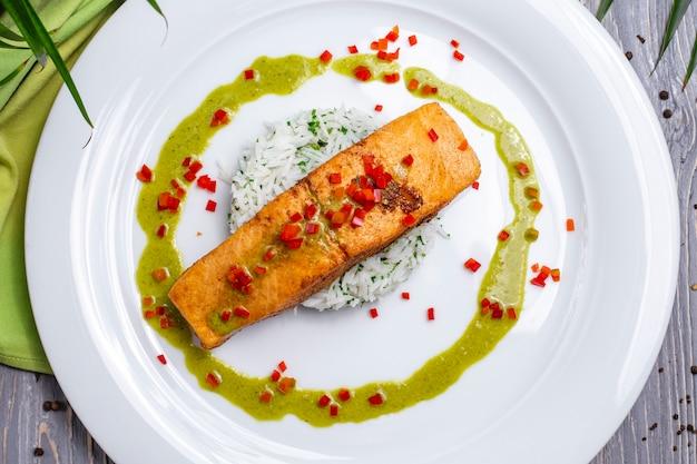Вид сверху жареная красная рыба с рисом и соусом на тарелке