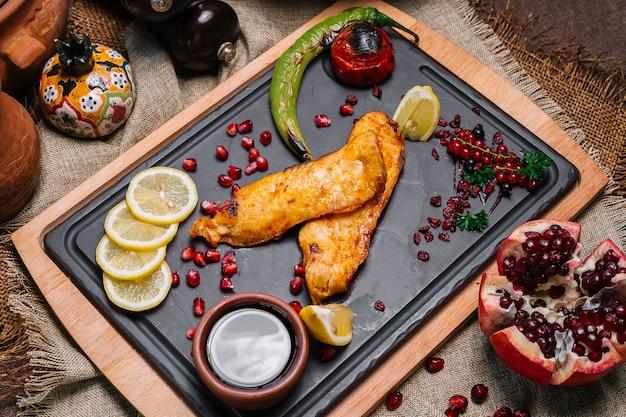 Вид сверху жареная рыба с помидорами и острым перцем гриль с гранатовыми ломтиками лимона и соусом наршараб