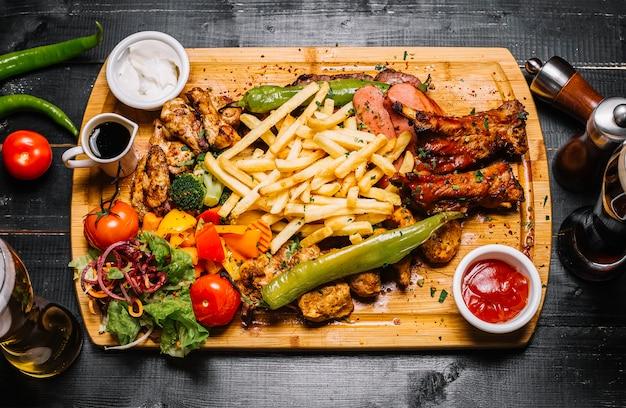 Вид сверху смесь мясных закусок с картофелем фри, овощами на гриле, салатом и соусами на доске