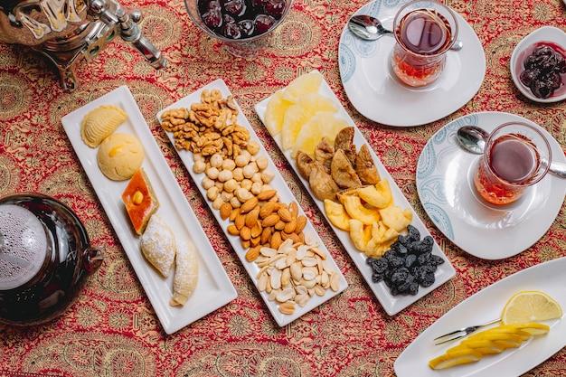 Вид сверху чайный набор сухофрукты печенье пахлава орехи с двумя стаканами чая