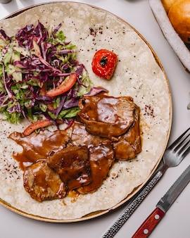 Вид сверху телятина в соусе на лаваш с овощным салатом