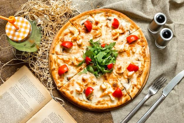 素朴なテーブルにチキンマッシュルームとチェリートマトにルッコラをトッピングしたピザのトップビュー