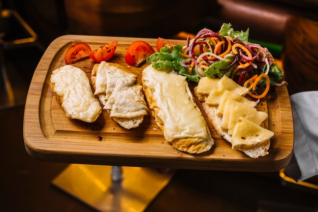 上面図、トマトと野菜のサラダのスライスとチーズトーストのトレイを保持している男