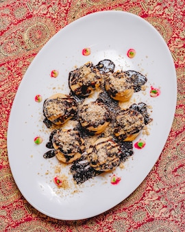 Вид сверху десертные профитроли с шоколадной глазурью и тертыми орехами
