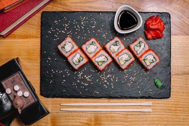 Вид сверху суши калифорнийский ролл с имбирем васаби и соевым соусом