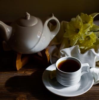 ホワイトティーポットの横にある白いカップで紅茶のカップ