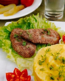 マッシュポテトの側面図と肉のカツレツ