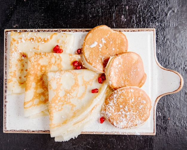 Блинчики и блины на деревянной доске с сахарной пудрой и гранатом на вид сверху