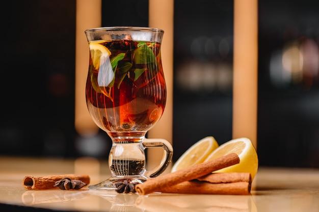 Фронтальный вид бодрящего бокала чая с корицей, лимоном и мятой
