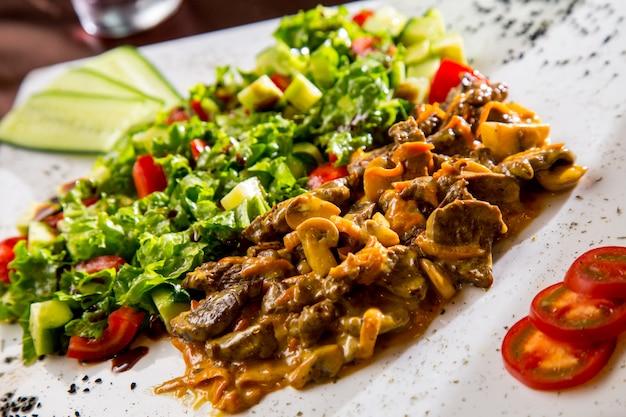 Вид спереди жареного мяса с грибами в соусе с овощным салатом и ломтиками помидора и огурца
