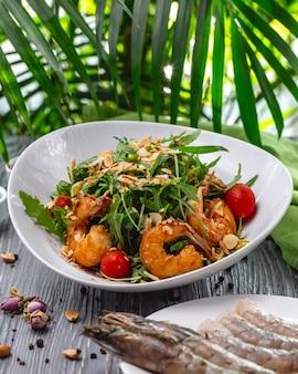 Вид спереди на салат с креветками, орехами, рукколой и помидорами черри