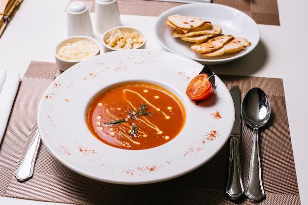 Вид спереди томатный суп с сыром и крекерами
