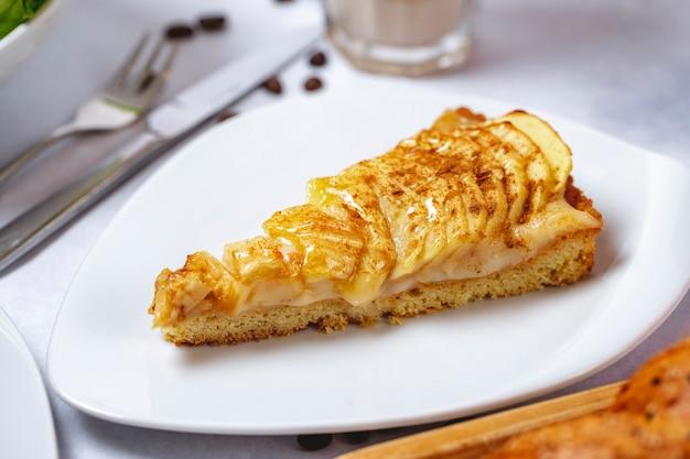 Вид сбоку яблочный пирог с кремом и корицей на тарелке