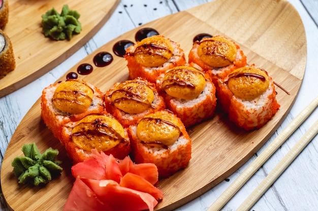 Вид сбоку запеченный калифорнийский рулет с крабовым мясом сливочный сыр тобико икорный соус васаби и имбирь на доске