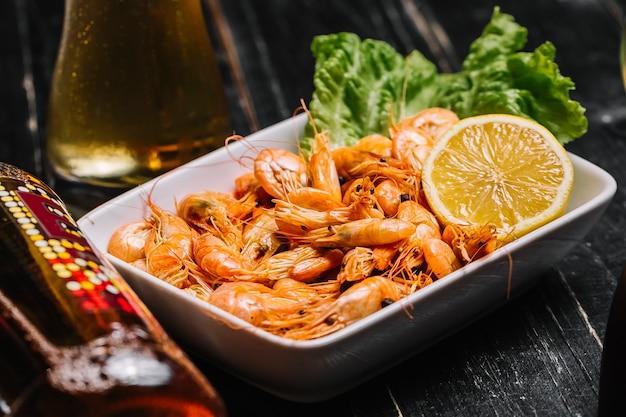 Вид сбоку вареные речные креветки на листе салата с лимоном