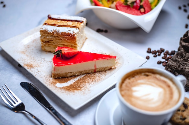 Вид сбоку корка из чизкейка с творожным клубничным желе и чашкой кофе на столе