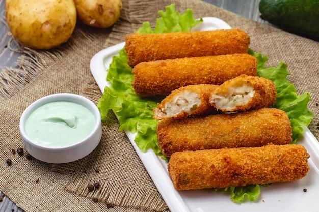 Вид сбоку куриные наггетсы на салат с соусом и неочищенным картофелем